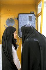 iranische Frauen beim telefonieren in einer oeffentlichen Telefonzelle