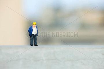 Plastic figurine of construction worker set on ledge