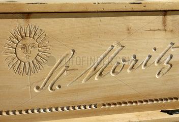 St. Moritz  Schweiz  Schriftzug St. Moritz und eine Sonne in Holz geschnitzt