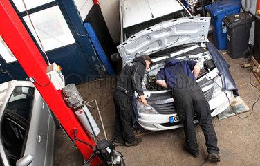 Kfz-Werstatt: Mechatroniker inspiziert eine nachgeruestete Fluessiggasanlage