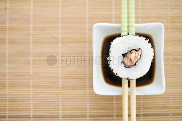 Single piece of maki sushi resting on chopsticks over sauce  overhead view
