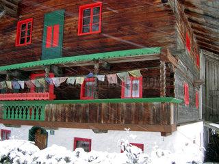 Tibetanische Gebetsfahnen an einem Bauernhaus in Tirol