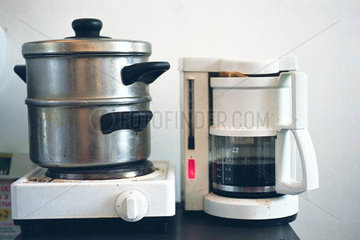 Steamer on hotplate next to coffee maker on counter