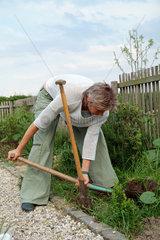 Frau beim Umgraben im Garten