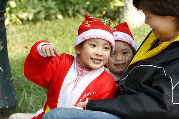 Zwei Kinder in Nikolauskostuemen in einem Park von Hanoi