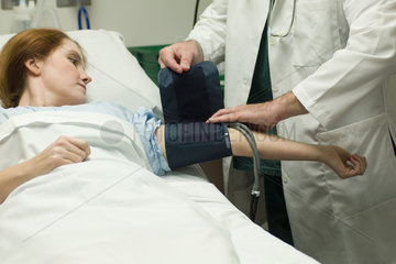 Doctor putting blood pressure cuff on patient in hospital
