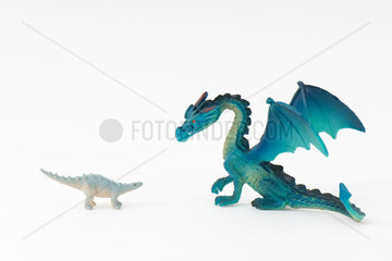 Toy dinosaur and toy dragon  face to face