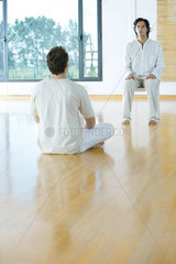 Two men facing each other in alternative therapy session