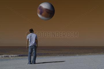 Man on beach looking up at alien world orbiting overhead against brown sky