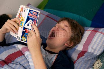 G__hnender Junge im Bett