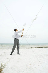Man at the beach holding up shovel  throwing sand  full length