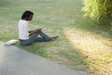 Young woman relaxing in park  text messaging with cell phone