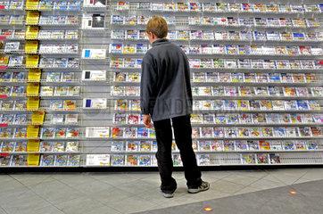 Junge vor Kaufhausregal mit Spielkonsolen-Programmen - model released -