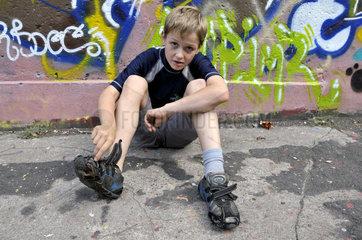 Junge mit kaputten Turnschuhen