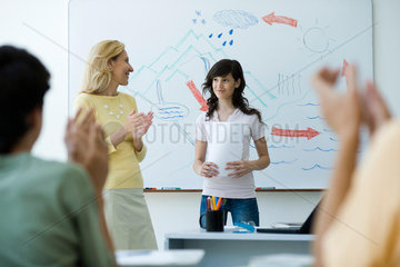 High school student finishing classroom presentation  classmates and teacher clapping