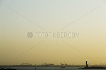 United States  New York City  New York Harbor at sunrise  Statue of Liberty visible in distance