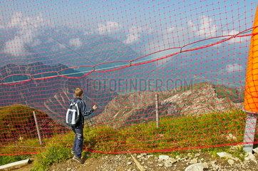 Zehnjaehriger Junge steht an einem Sicherheitsnetz vor einem Abgrund am Nebelhorn