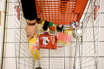 Shopper placing groceries in shopping cart