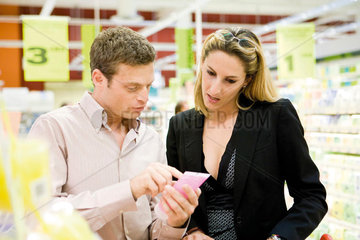 Couple in store carefully reviewing product label