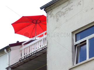 Dachterrasse mit rotem Sonnenschirm