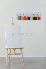 Blank canvas on easel  poster of colored pencils in background