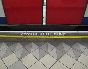 Mind the gap warning painted on the edge of the subway platform in the London Underground