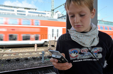Junge mit Handy im Stuttgarter Hauptbahnhof