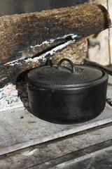 Cast iron pot sitting beside fireplace