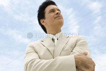 Businessman with arms folded  looking up  smiling  low angle view