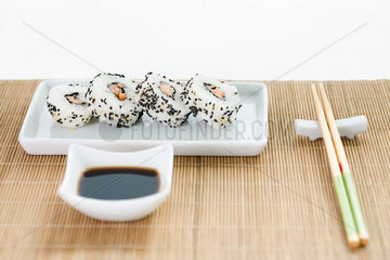 Maki sushi with soy sauce and chopsticks arranged on bamboo placemat