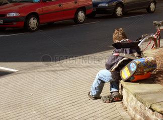 Schueler nach der Schule wartet auf seine Mutter