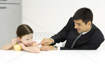 Girl protecting bowl of cereal while father teases her