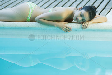 Young woman lying next to pool