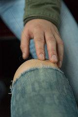 Fingerspitzen beruehren nacktes Knie