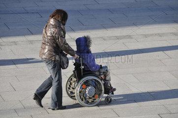 Frau im Rollstuhl wird geschoben