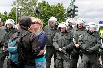Kuessendes Paerchen vor behelmten Polizisten in Kampfanzuegen