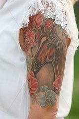 Hannover  Deutschland  Pferde-Tattoo auf dem Oberarm einer Frau
