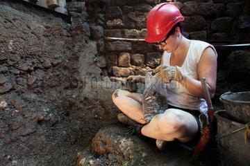 Archaeologische Zone in Koeln: Archaeologiestudentin graebt an der Ostseite der Mikwe.