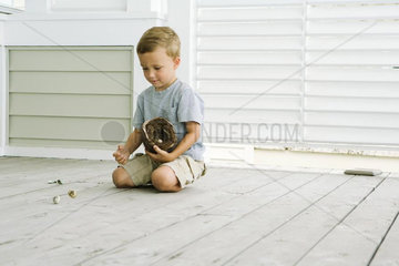 Boy kneeling on the ground  spilling eggs out of bird's nest