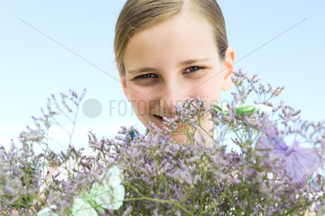 Preteen girl looking over top of flowering plant  smiling at camera