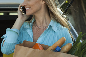 Woman using cell phone and holding bag of groceries
