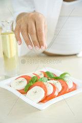 Woman preparing dish of Caprese salad  sprinkling pepper
