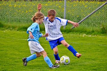 Maedchen und Jungen beim Fussballspielen