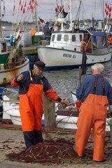 Fischer reinigt Netz auf Fehmarn