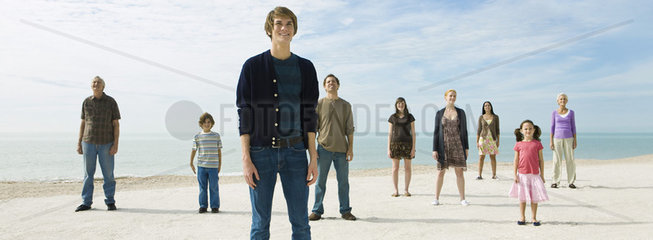Group of individuals standing on beach  smiling optimistically