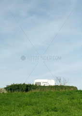 RV parked behind low wall in rural setting