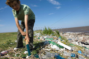 Boy cleaning up polluted shore with shovel  low angle view