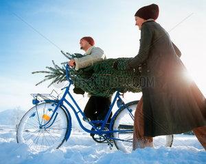 Junges Paar mit Fahrrad und einem Weihnachtsbaum