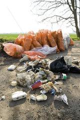 Trash dumped outdoors  full bags of trash in background result of cleanup effort