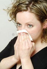 Berlin  junge Frau putzt sich die Nase